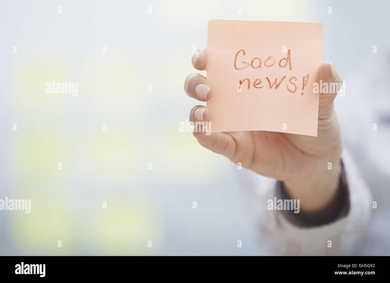Woman holding sticky note with Good news text Stock Photo