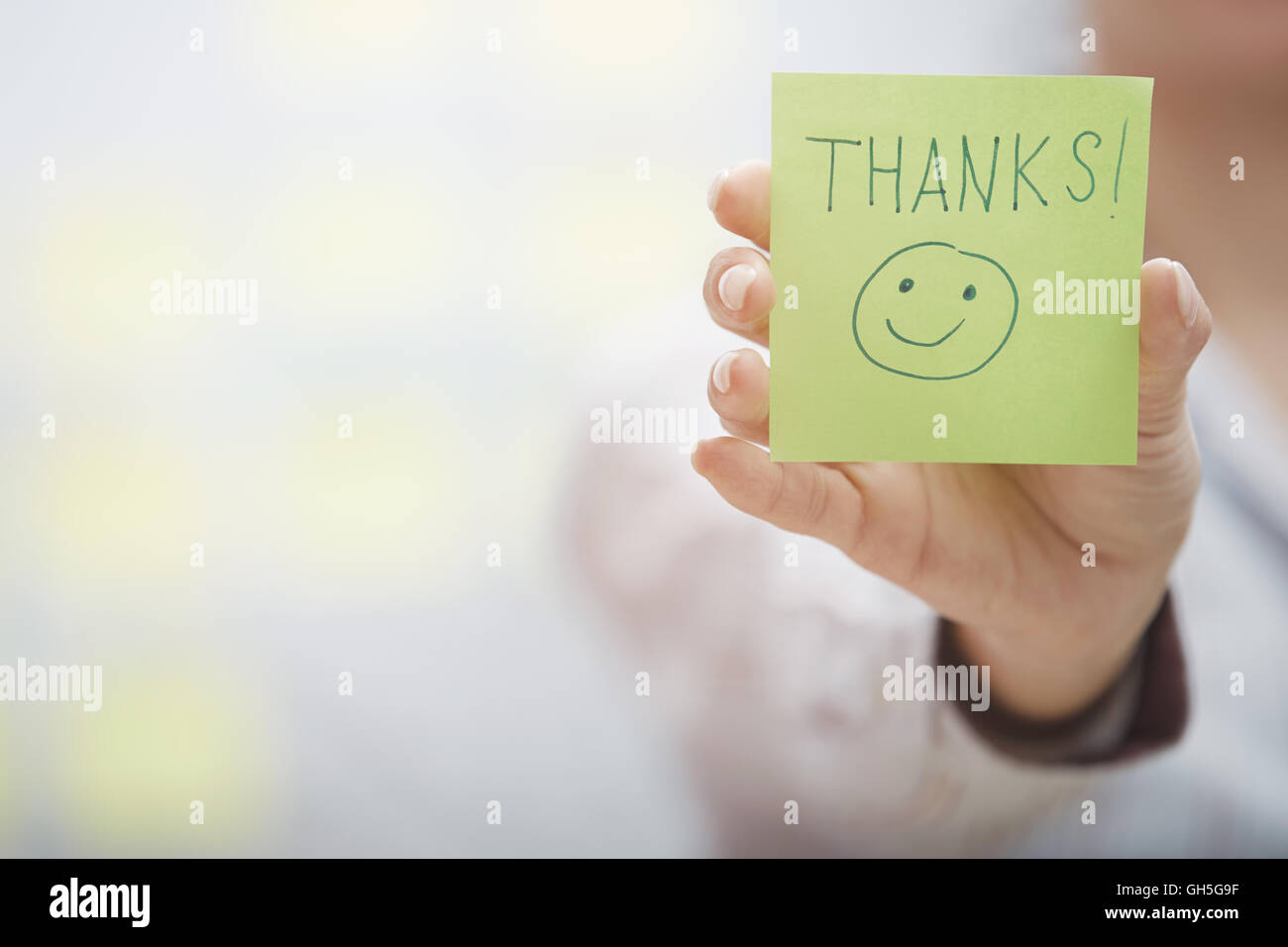 Woman holding sticky note with Thanks text Stock Photo