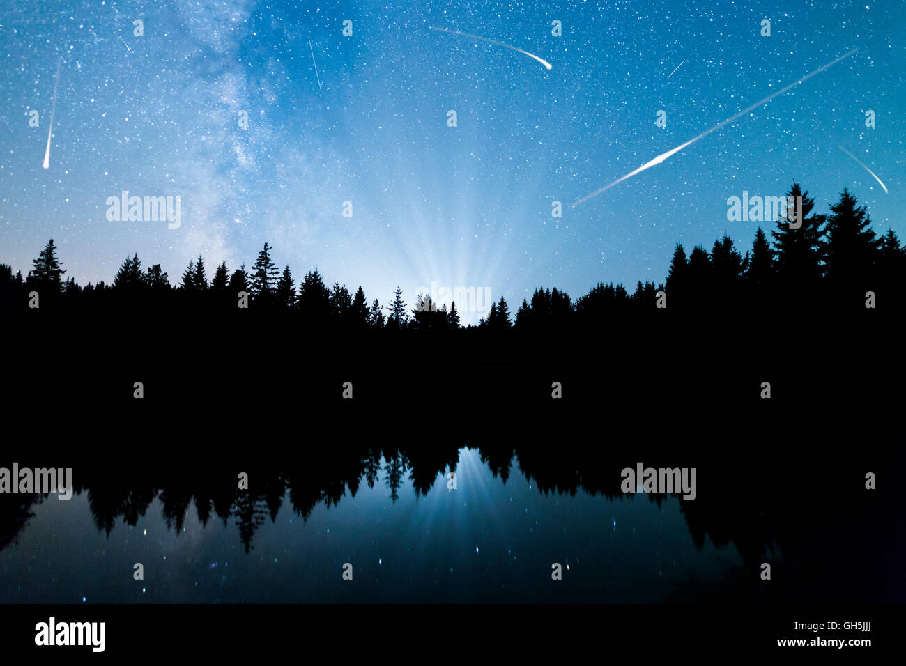 A view of the stars of the Milky Way with a silhouette of a pine trees forest near a lake in the mountain. Falling Stock Photo