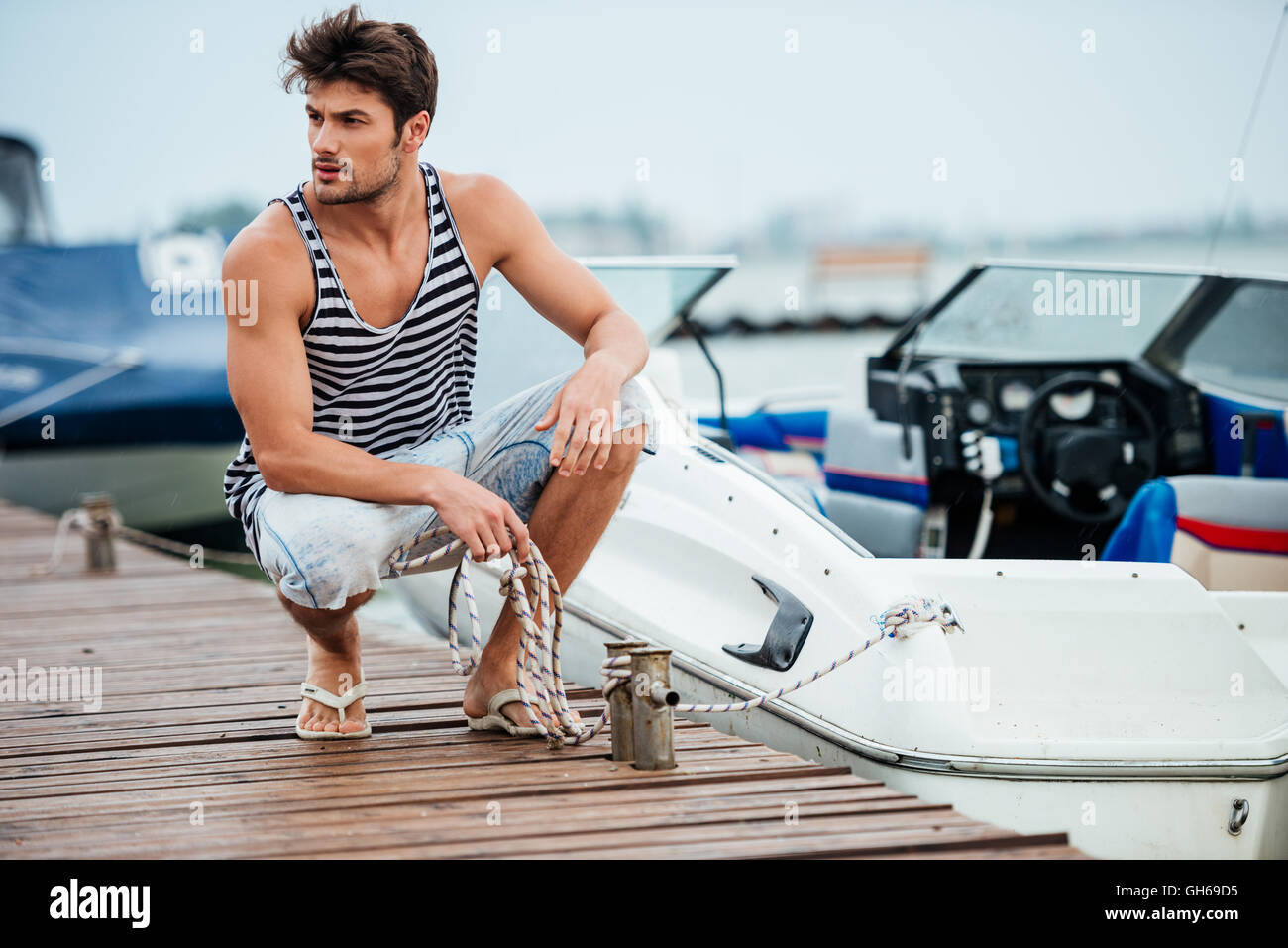 Young handsome man preparing boat to start a journe at the pier - Stock Image