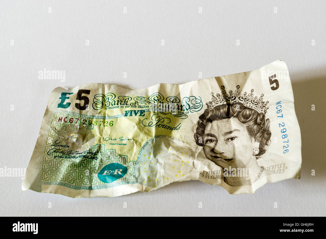 A crumpled paper five pound note of UK currency - Stock Image