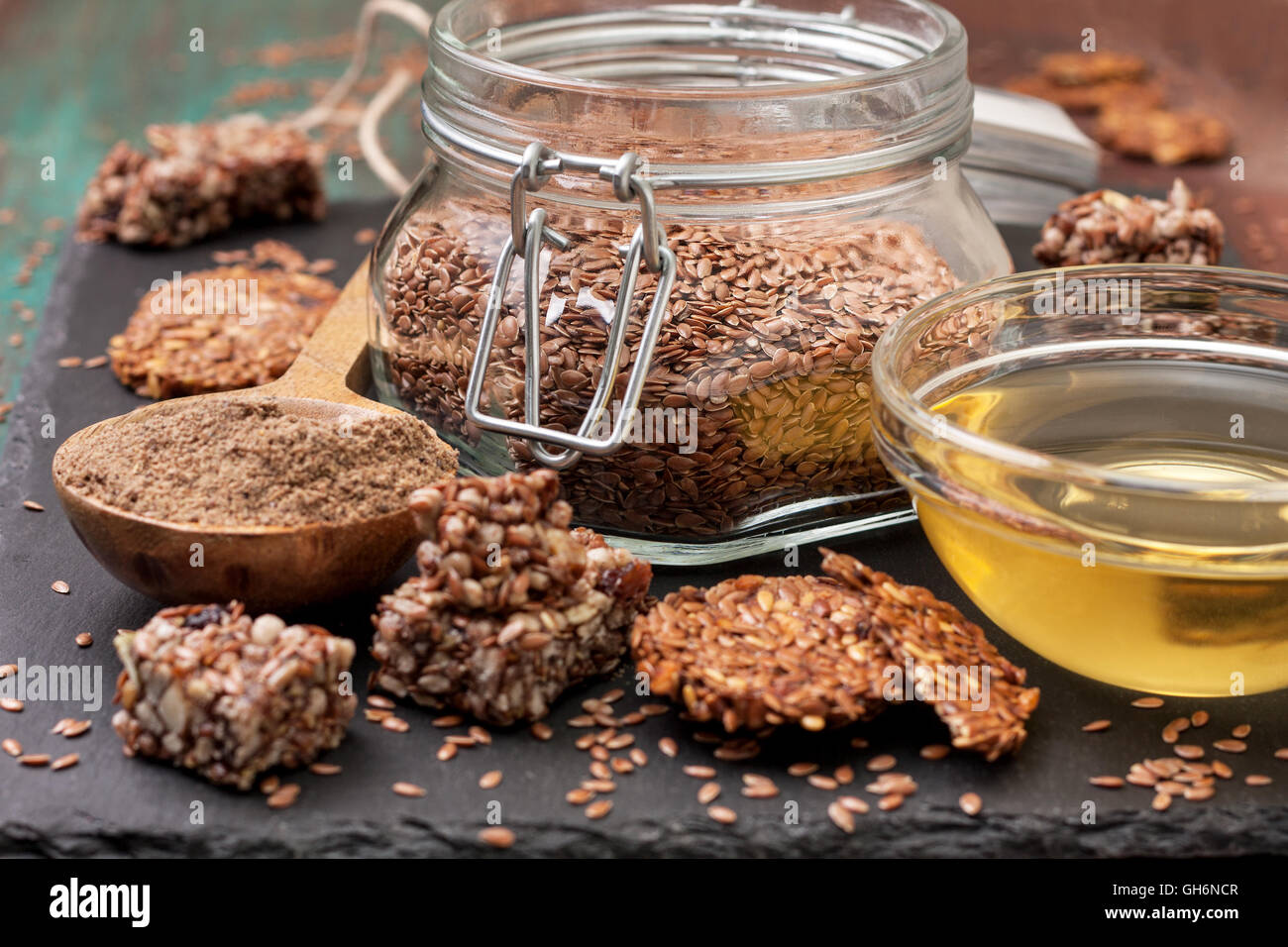 flax seeds and products thereof: linseed oil, flax flour, energy bars and crackers from flax seeds on a dark a stony - Stock Image