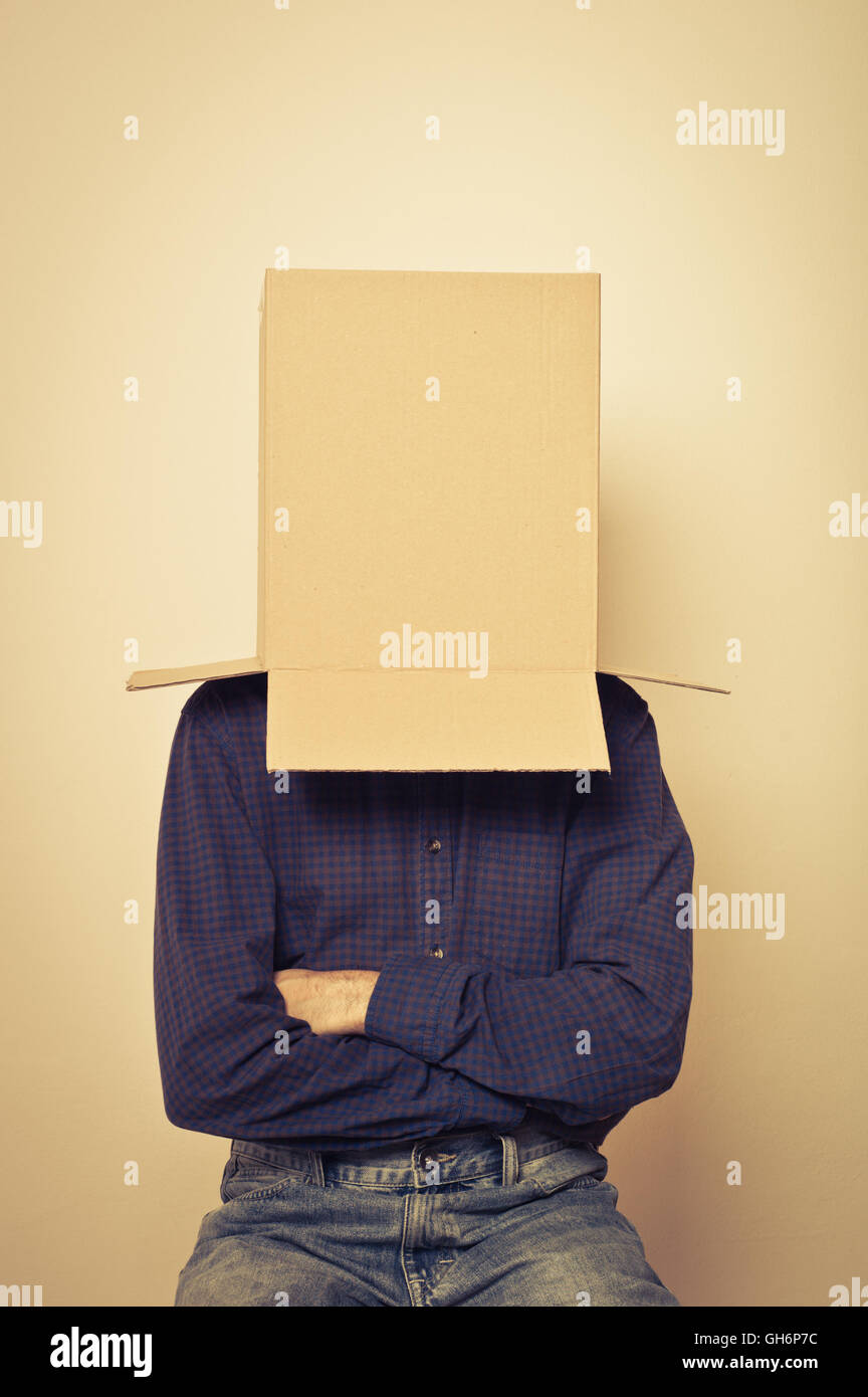 man with a blank box over his head, various concept: thinking, shy, afraid - Stock Image