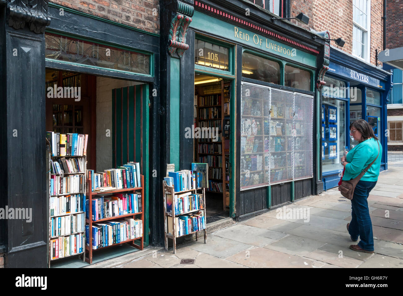 Customer looking at books stacked outside Reid of Liverpool secondhand bookshop. Stock Photo