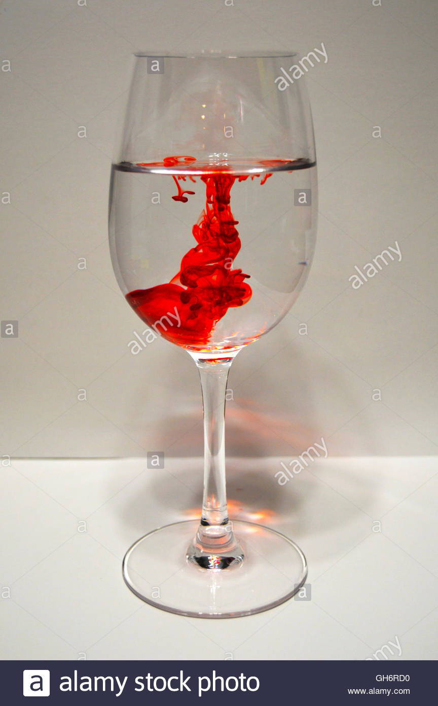 Wine glass full of water with drops of red food coloring Stock Photo ...