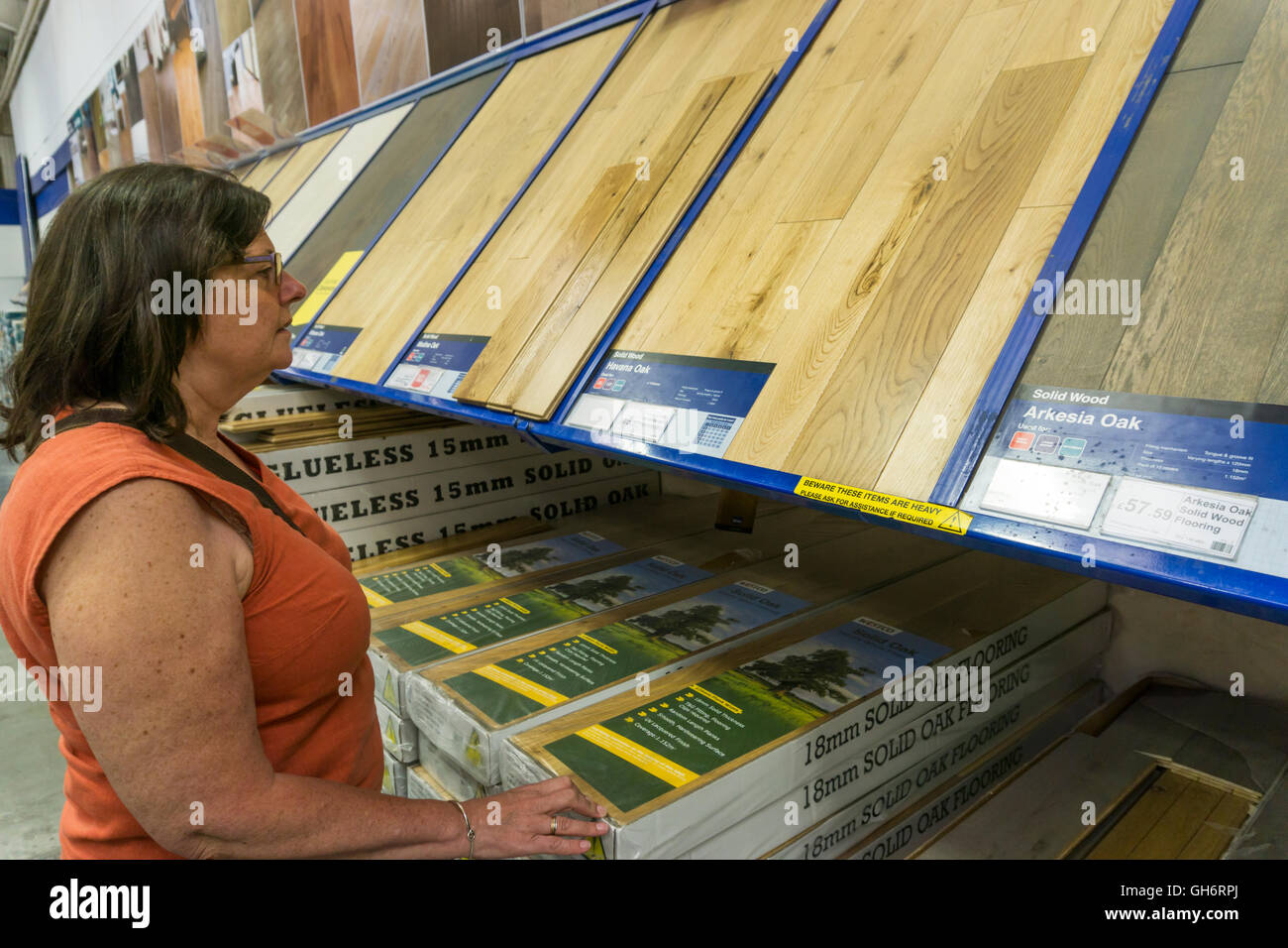 Woman looking at a display of laminate wooden flooring in a branch of Wickes DIY stores. - Stock Image