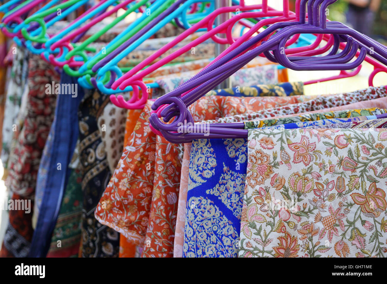 floral pattern clothes on hangers - Stock Image