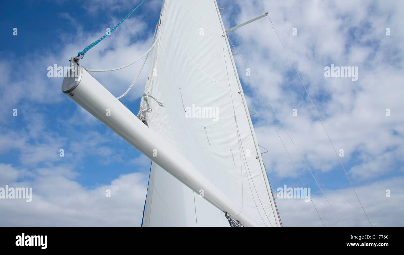Mainsail on a sailboat against a blue sky with clouds. - Stock Image