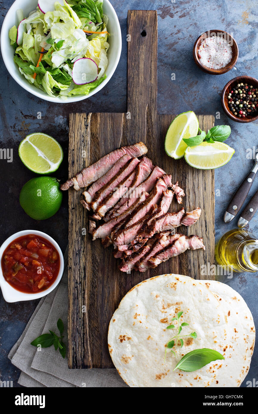 Cooking steak tacos with sliced meet - Stock Image