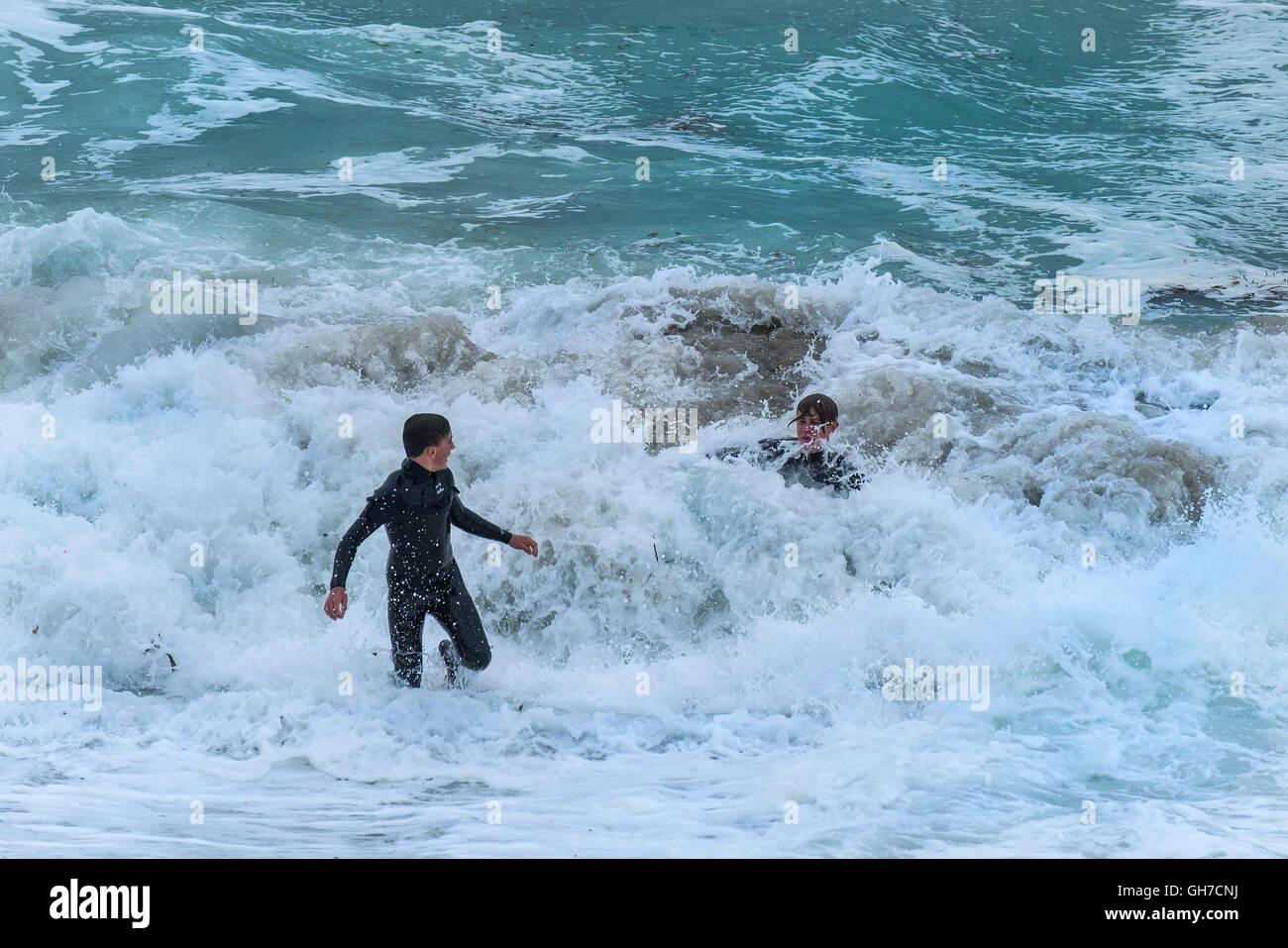 Two teenagers playing in very rough waves. - Stock Image