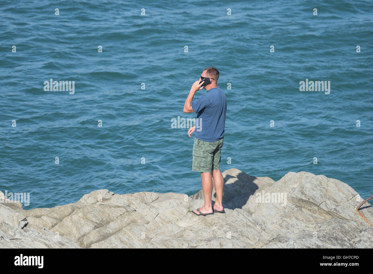 A holidaymaker uses a mobile phone as he stands on rocks near the sea. - Stock Image