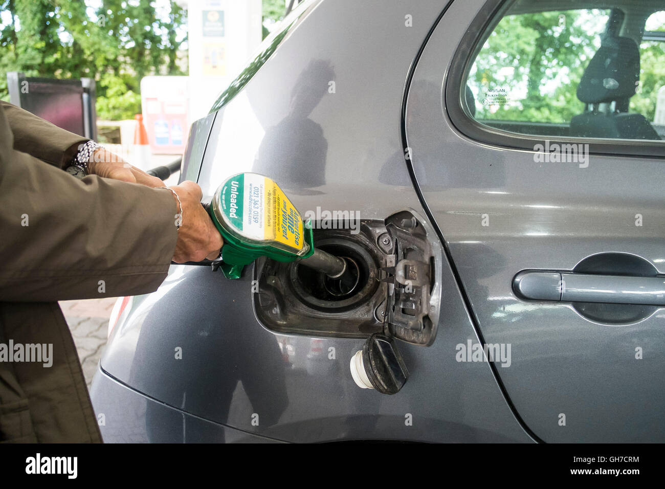 A customer filling a car with petrol. - Stock Image