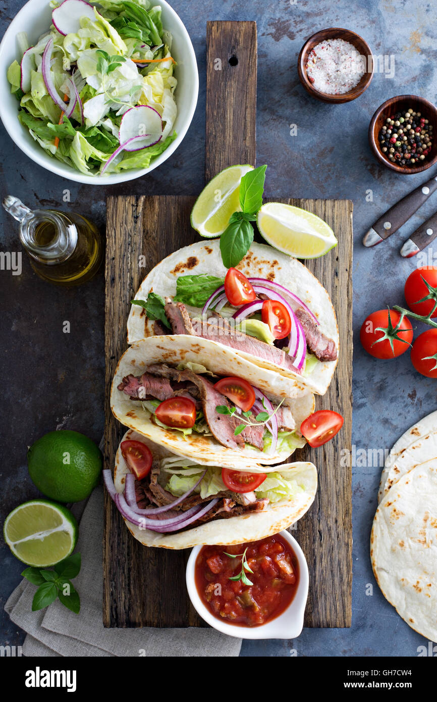 Steak tacos with sliced meet, salad and tomato salsa - Stock Image