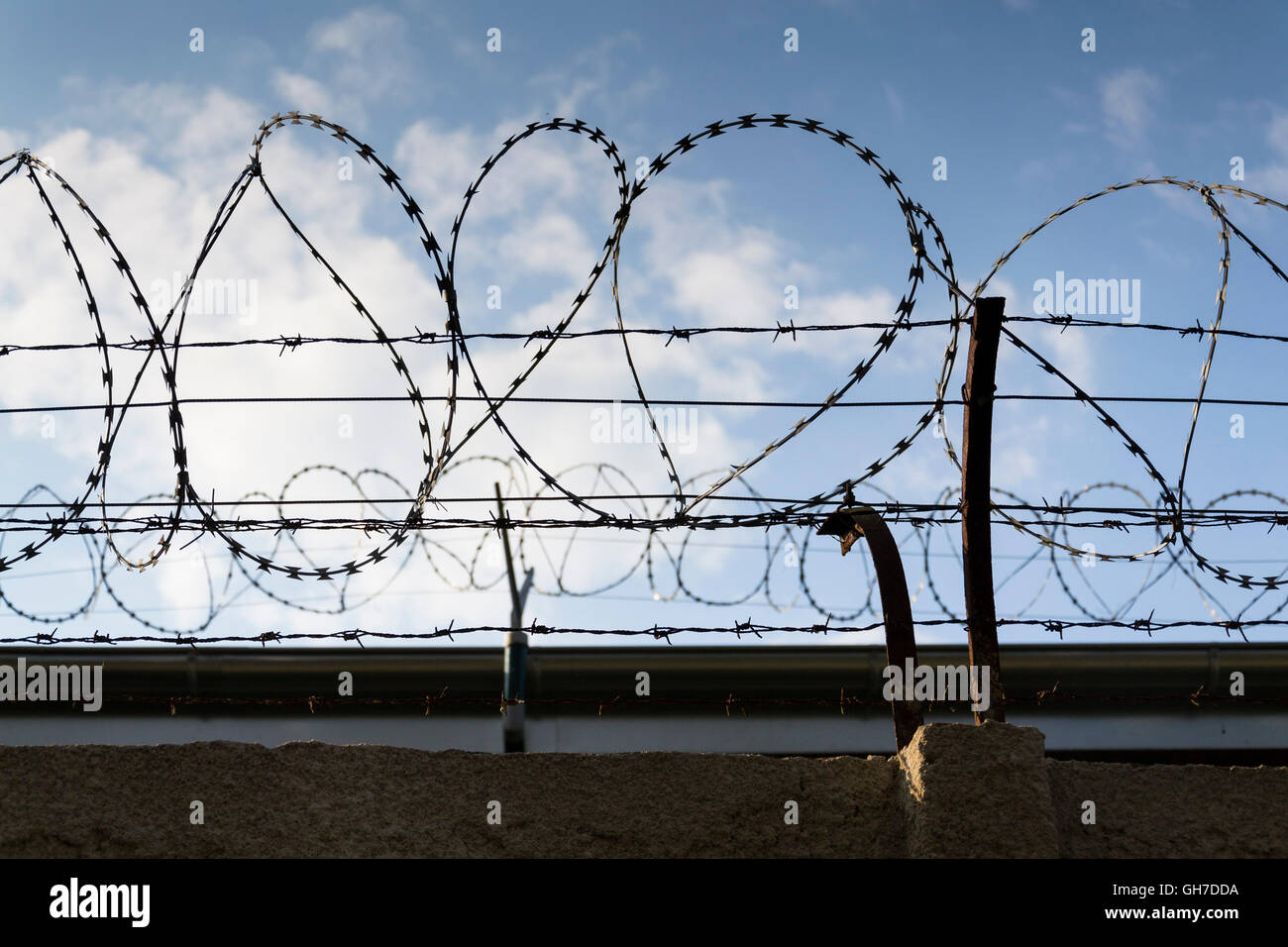 Prison wall barbed wire fence detail with blue sky in background ...
