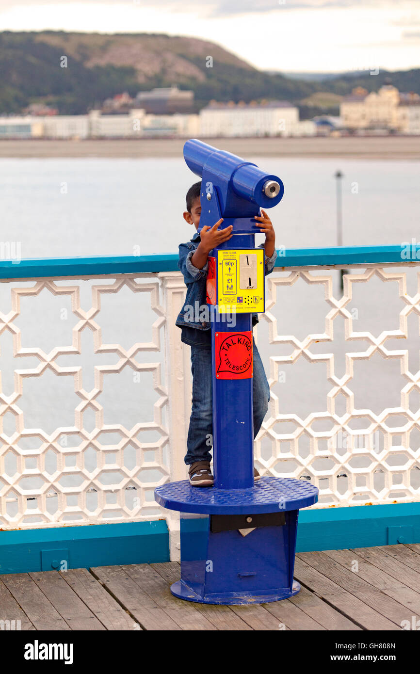 A young boy playing hide and seek behind a telescope on Llandudno  Pier, Wales, UK - Stock Image