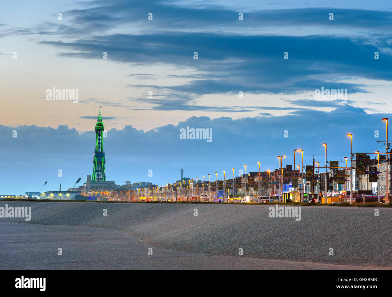 Blackpool tower illuminated in green light at the end of promenade. - Stock Image