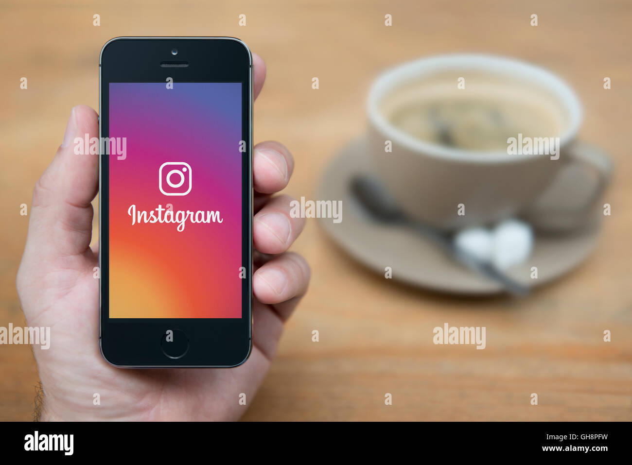 A man looks at his iPhone which displays the Instagram logo, while sat with a cup of coffee (Editorial use only). - Stock Image