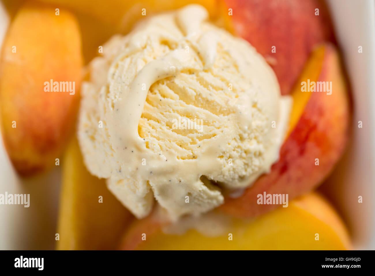 Vanilla ice cream and fresh peaches - Stock Image