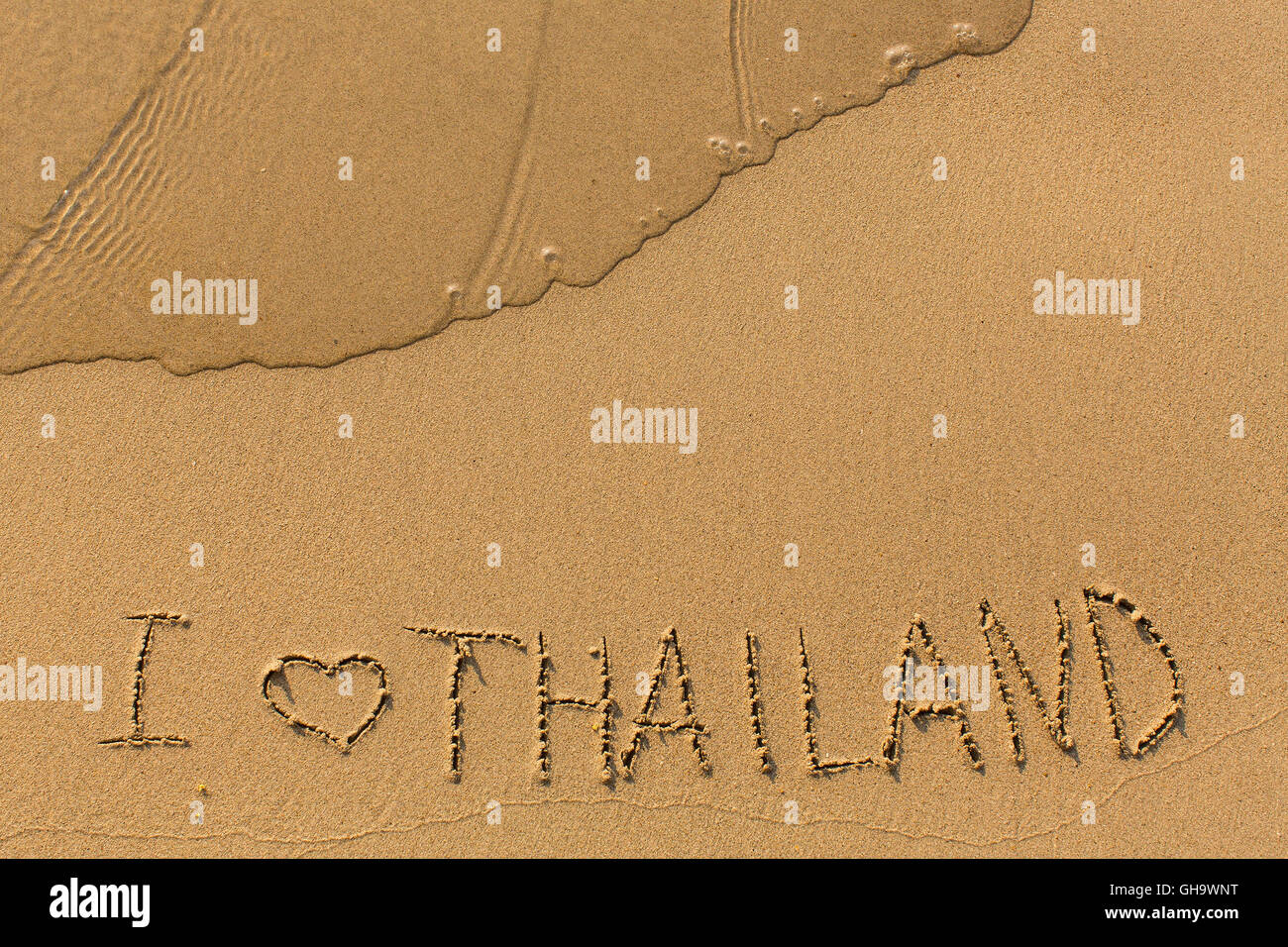 I love Thailand - inscription on a golden sand beach with a gentle surf. - Stock Image