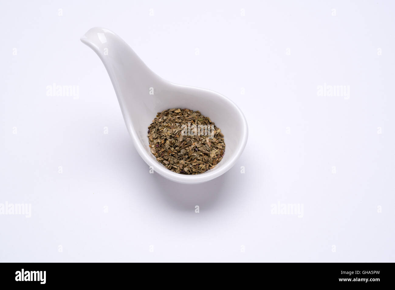 Monotone dry Basil 1 tablespoon in a white spoon on the white background - Stock Image
