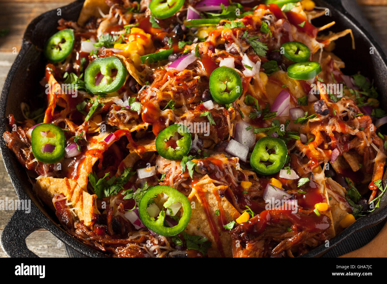 Homemade Barbecue Pulled Pork Nachos with Cheese and Peppers - Stock Image