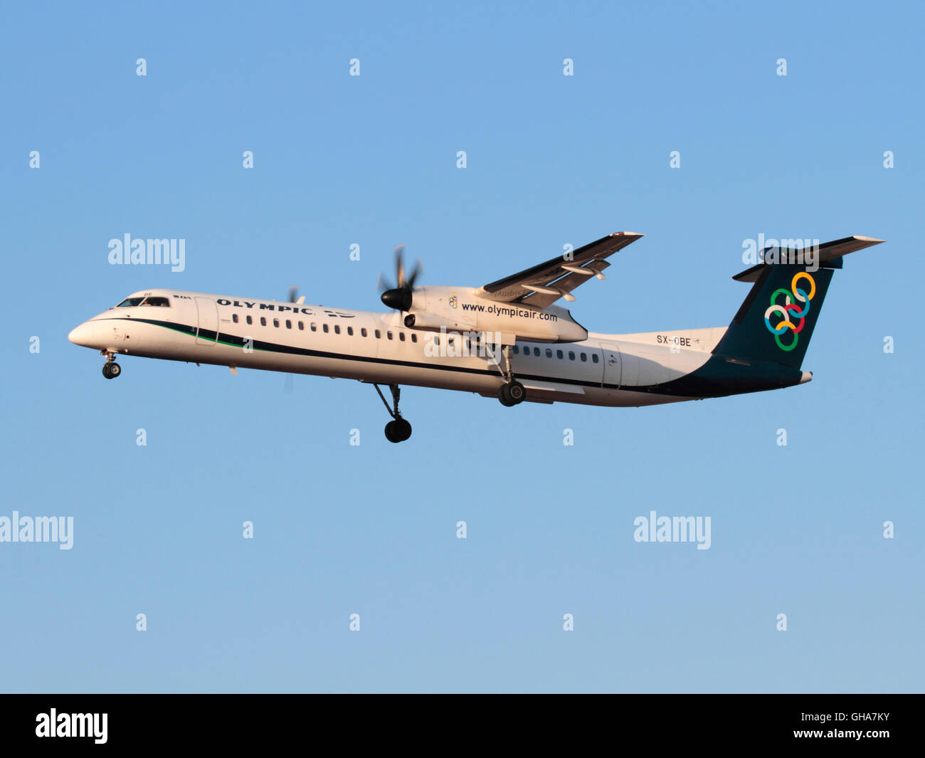 Olympic Air Bombardier Dash 8-Q400 turboprop regional airliner on approach at sunset - Stock Image