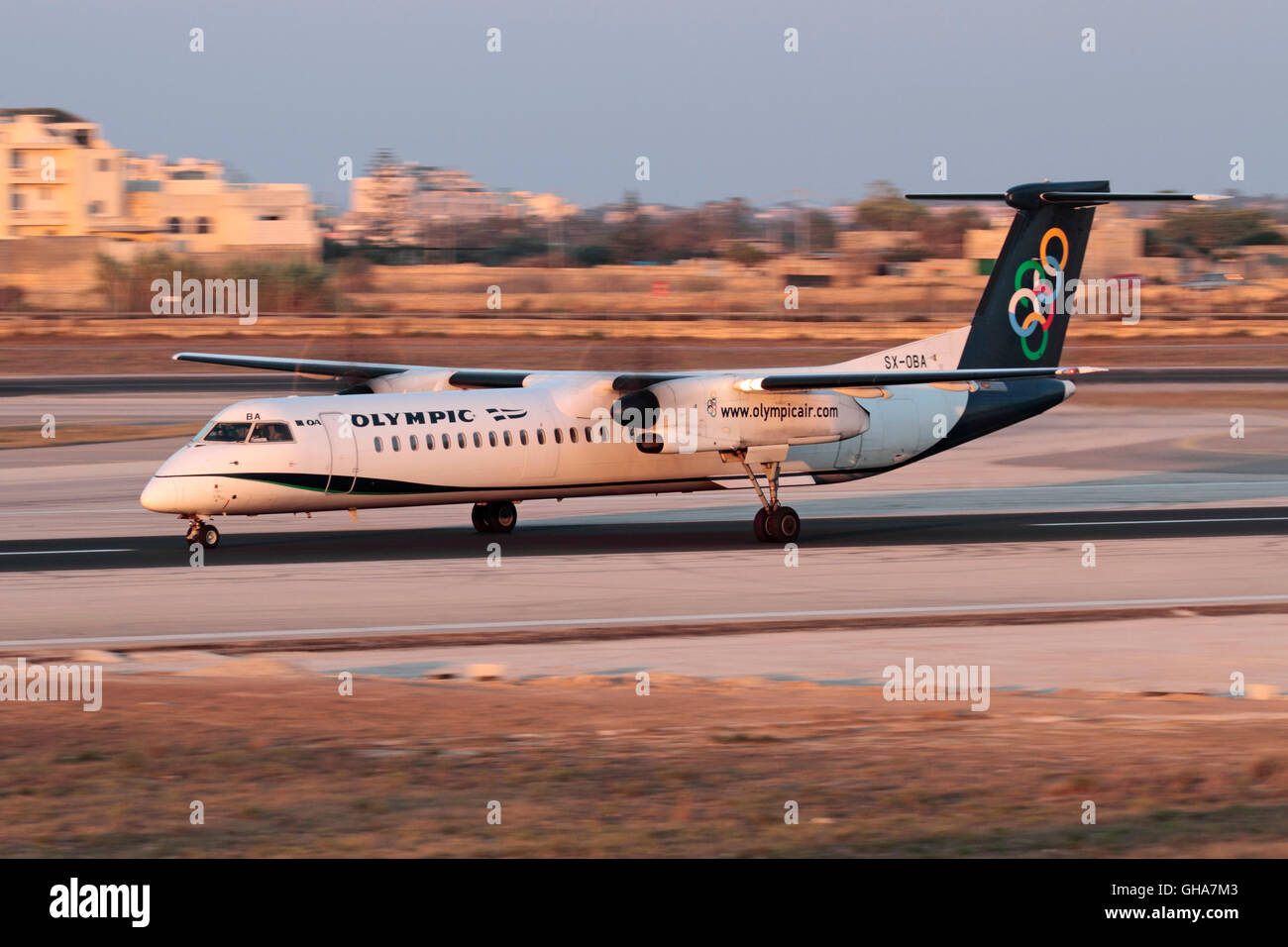 Olympic Air Bombardier Dash 8-Q400 turboprop plane taking off from Malta at sunset. Slow shutter speed used for - Stock Image