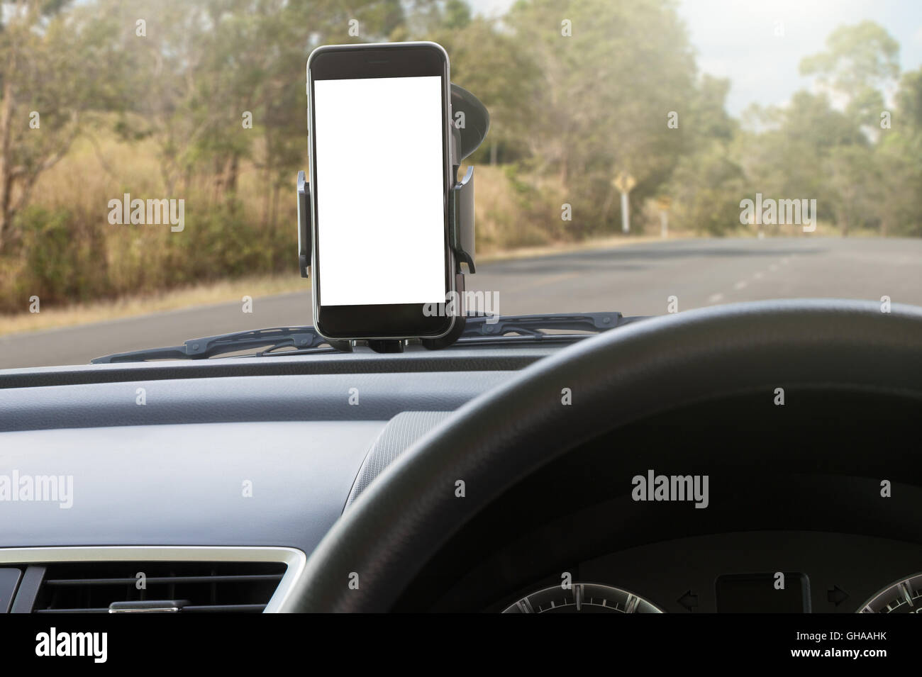 phone and mounted holder in car on rural road - Stock Image