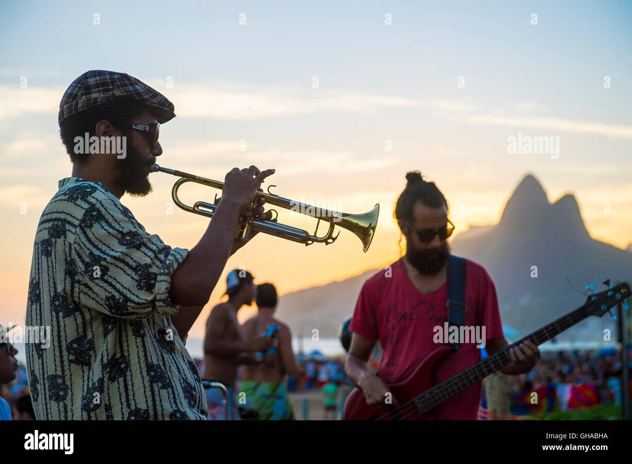 RIO DE JANEIRO - FEBRUARY 21, 2015: Silhouette of a musician playing his horn to an audience at the popular Arpoador Stock Photo