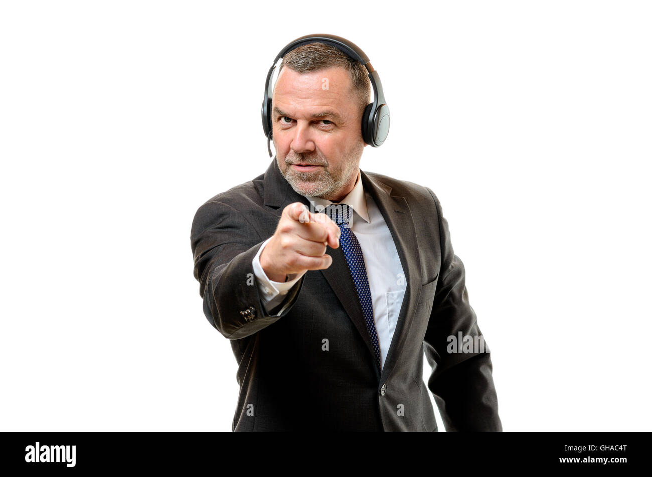 Irate middle-aged businessman wearing headphones pointing a finger of blame as he identifies something or makes Stock Photo