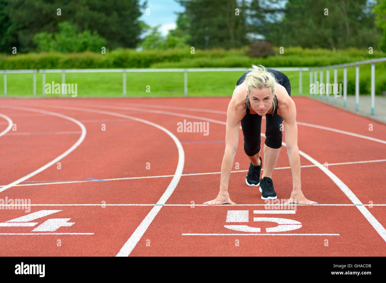 Athletic woman crouched down in the starter position on a race track at a sporting venue looking up at the camera - Stock Image