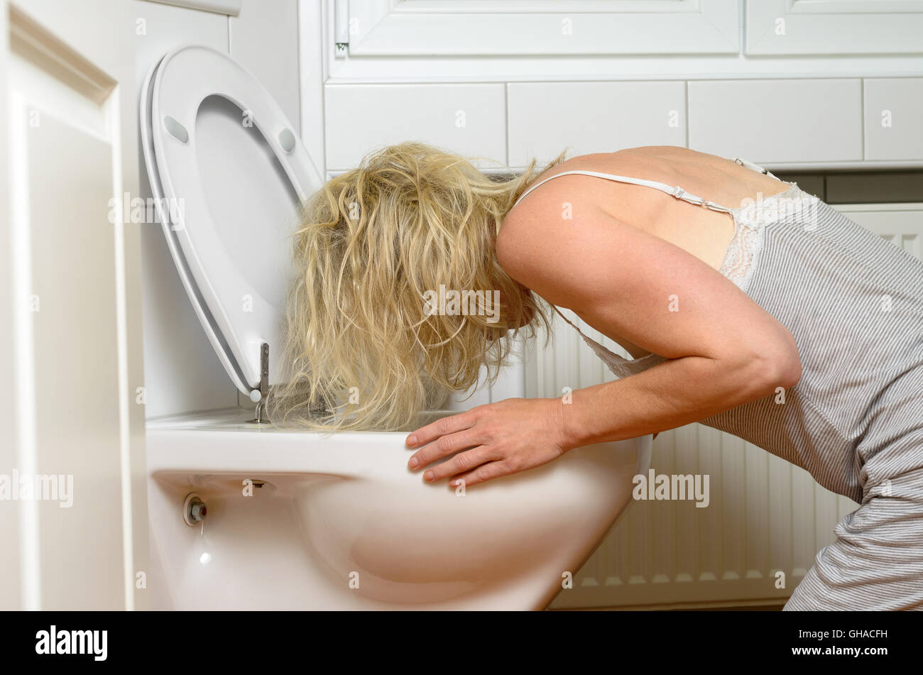 Blond woman in a grey dress kneeling down vomiting into a toilet conceptual of an illness or drunkenness after a Stock Photo