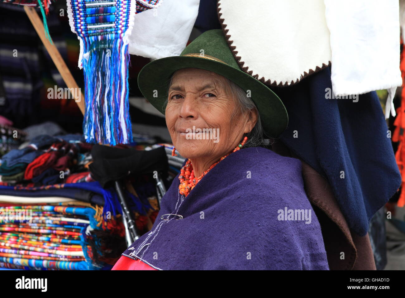 An elderly Ecuadorian woman in traditional dress, sits by her handmade clothes stall in Otavalo Market - Stock Image