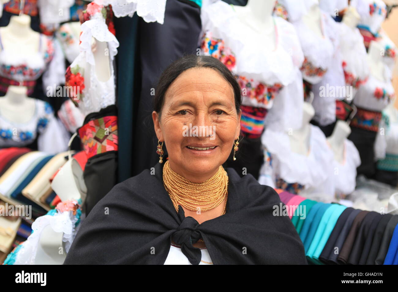 Older woman in traditional Ecuadorian dress, standing outside her handmade clothes stall in Otavalo market - Stock Image