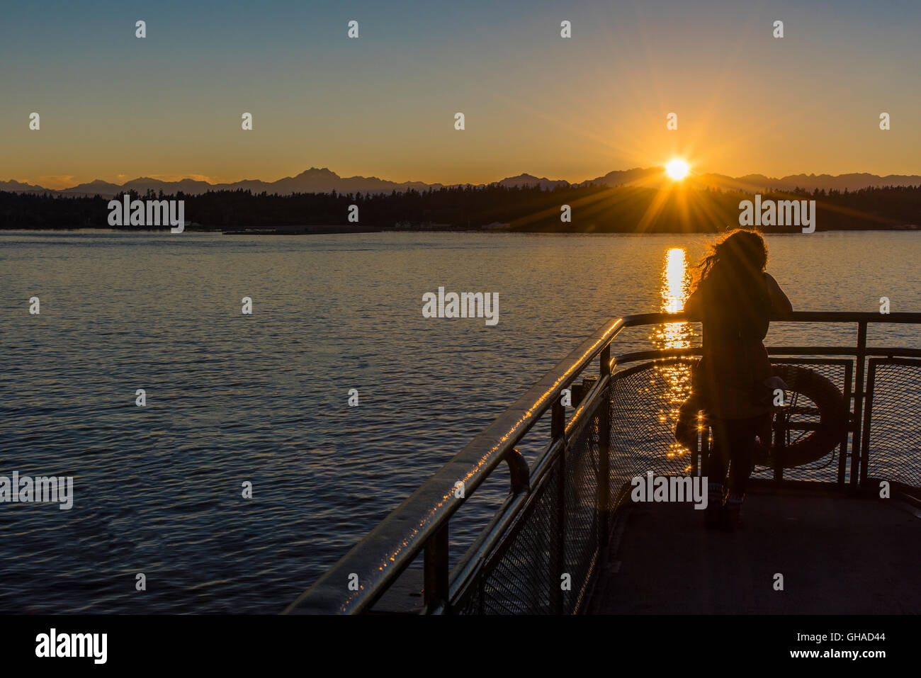 Young girl watching the sunset on the Elliott Bay from the ferry, Seattle, Washington, USA Stock Photo