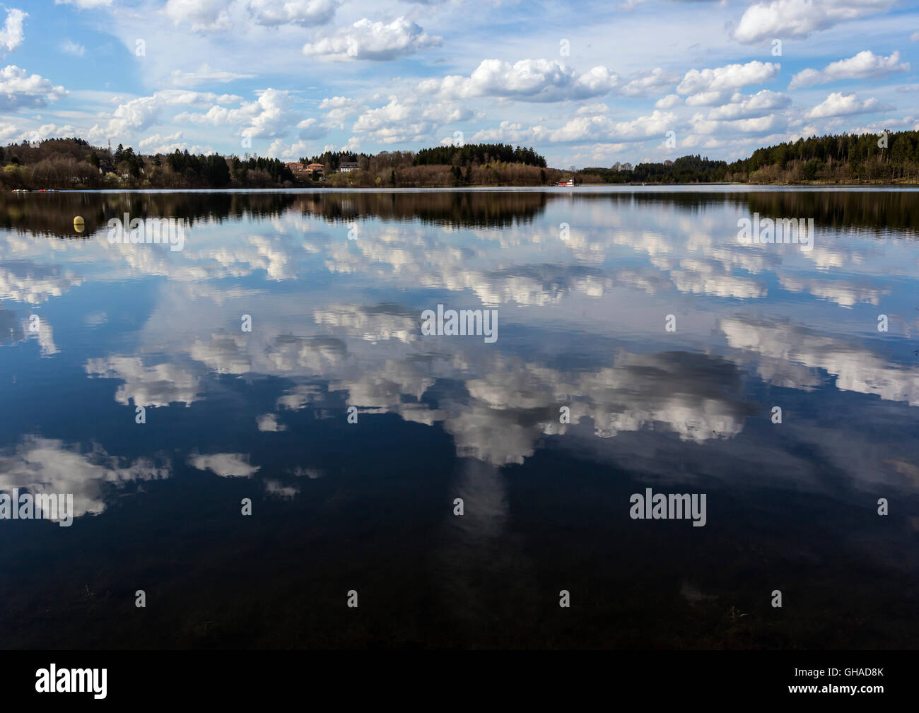 Cloud reflections on a still lake - Stock Image