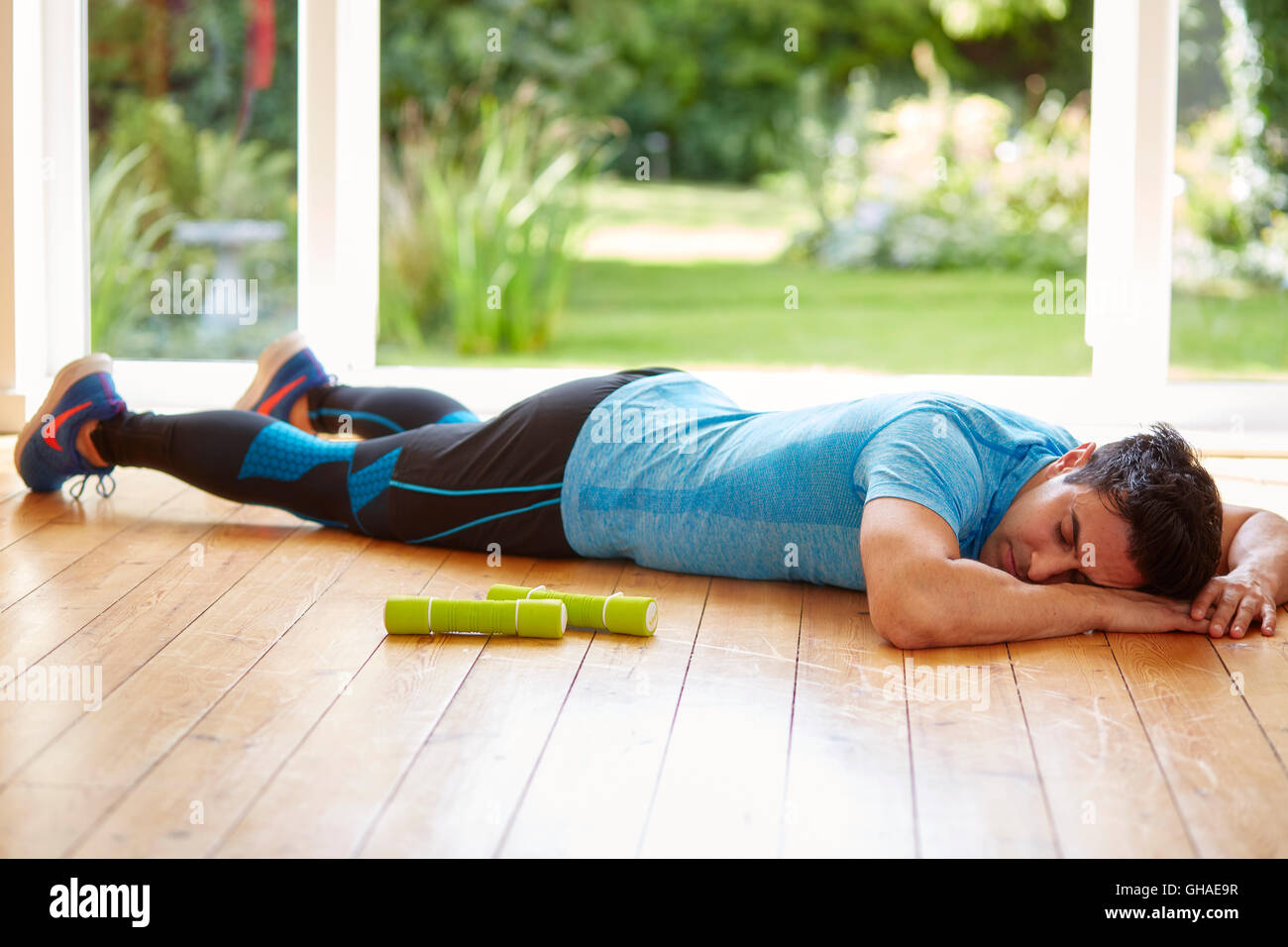 Man laid out exhausted after exercising - Stock Image