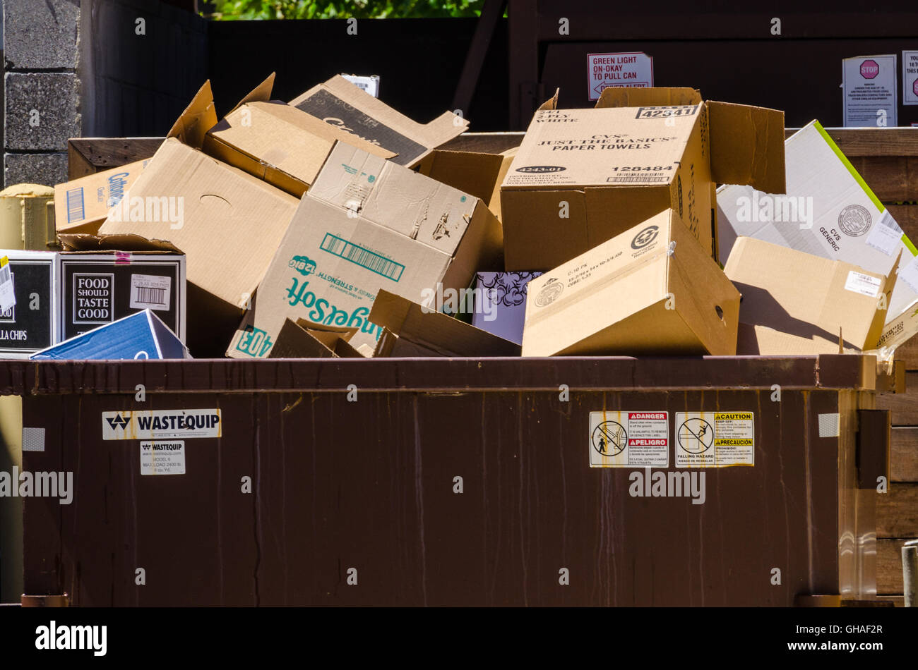 A trash receptacle full of cardboard boxes - Stock Image