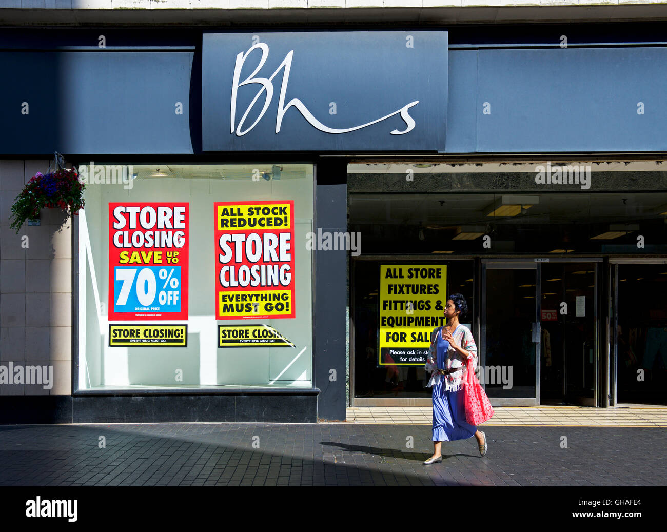 Woman walking past branch of BHS, British Home Stores, holding closing down sale, Middlesborough, North Yorks, England - Stock Image