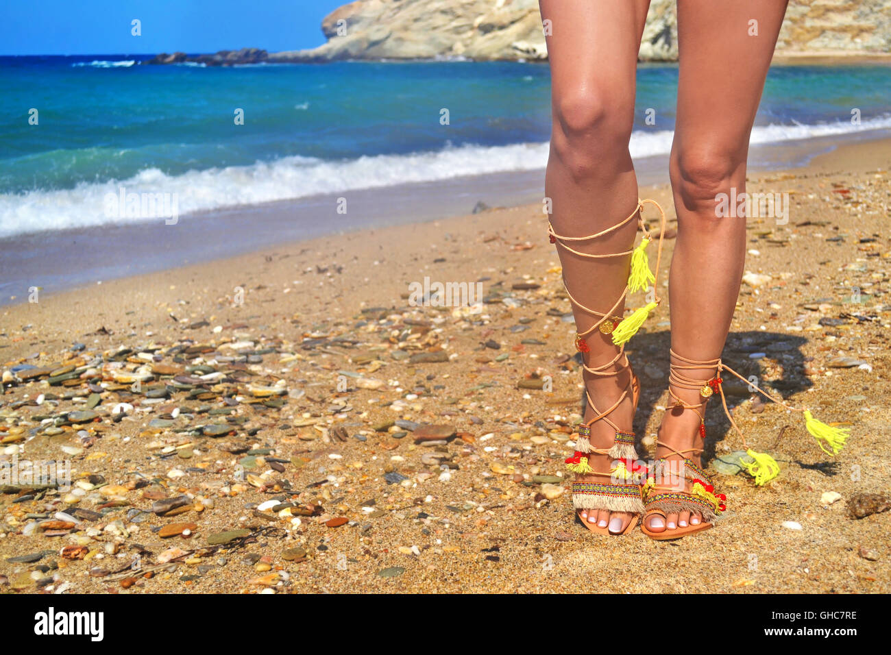 4ab547221335 model advertises bohemian greek sandals at the beach - summer shoes  advertisement - Stock Image