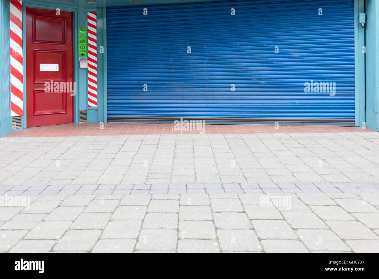A red door and a blue roller over a barbers shop window - Stock Image