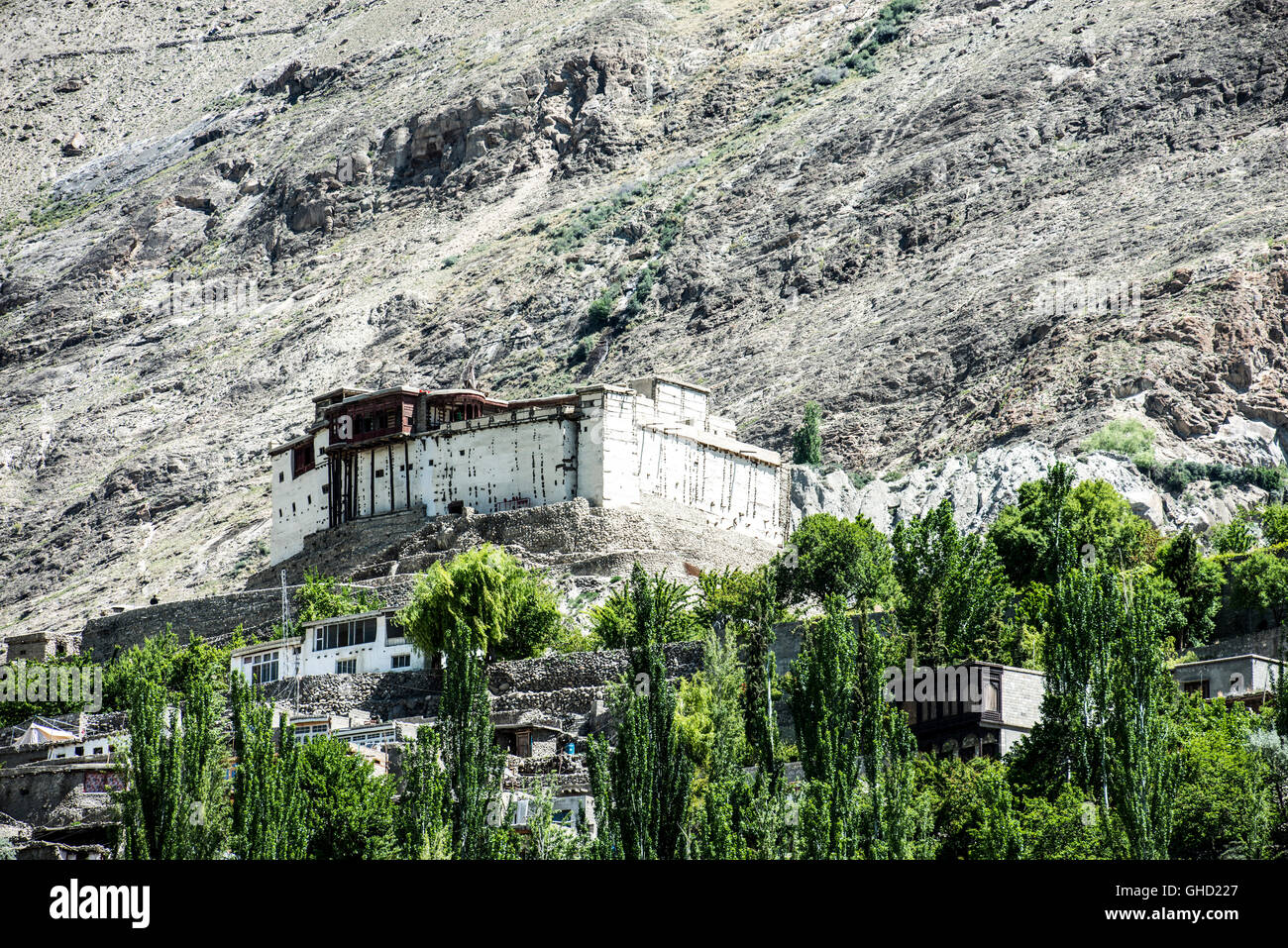 Baltit fort in Karimabad surrounded by poplars, with a back drop of a a barren cliff face - Stock Image