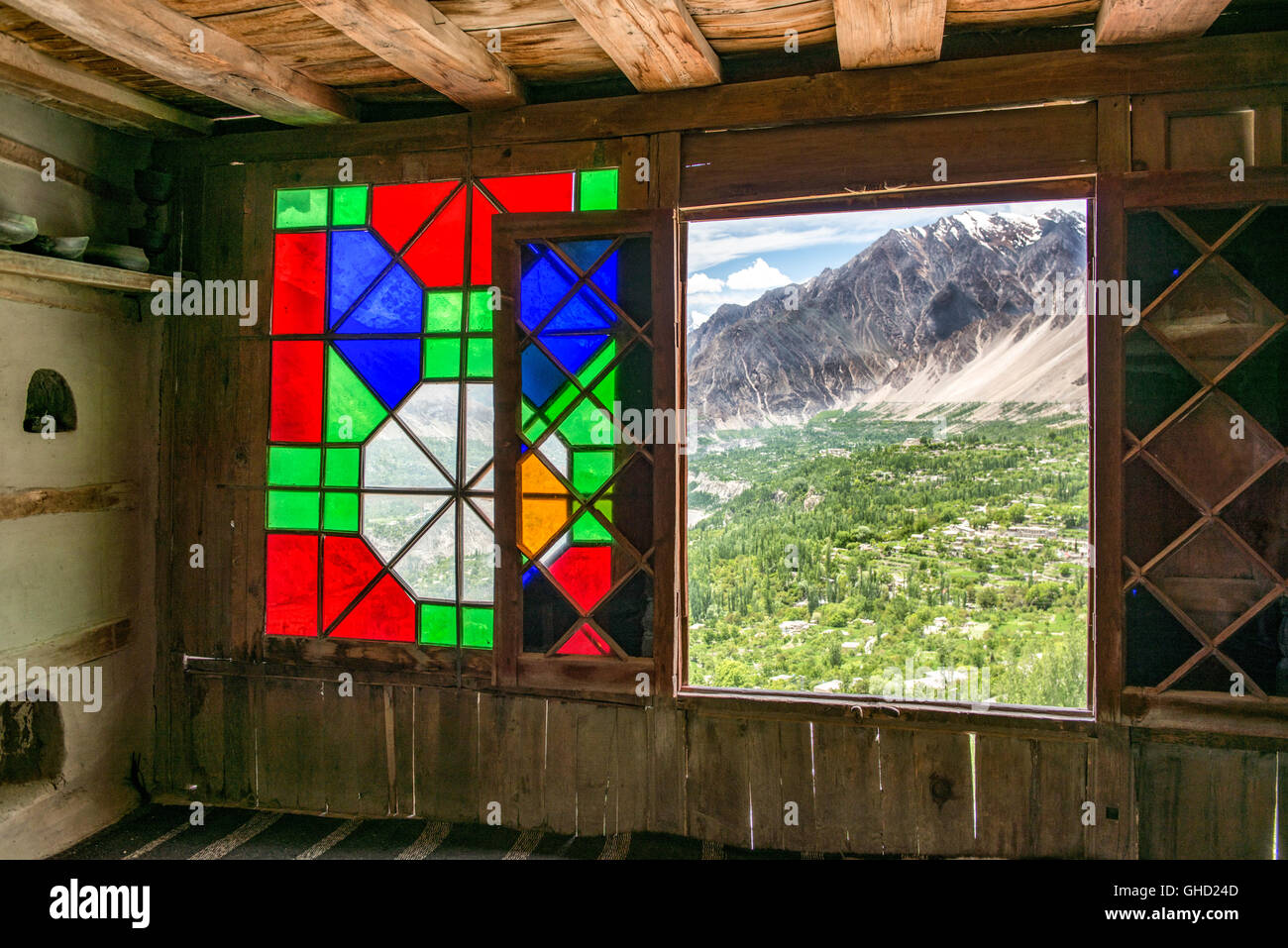 Stained glass window in the Baltit fort in Karimabad, northern Pakistan with a view over the Hunza valley - Stock Image