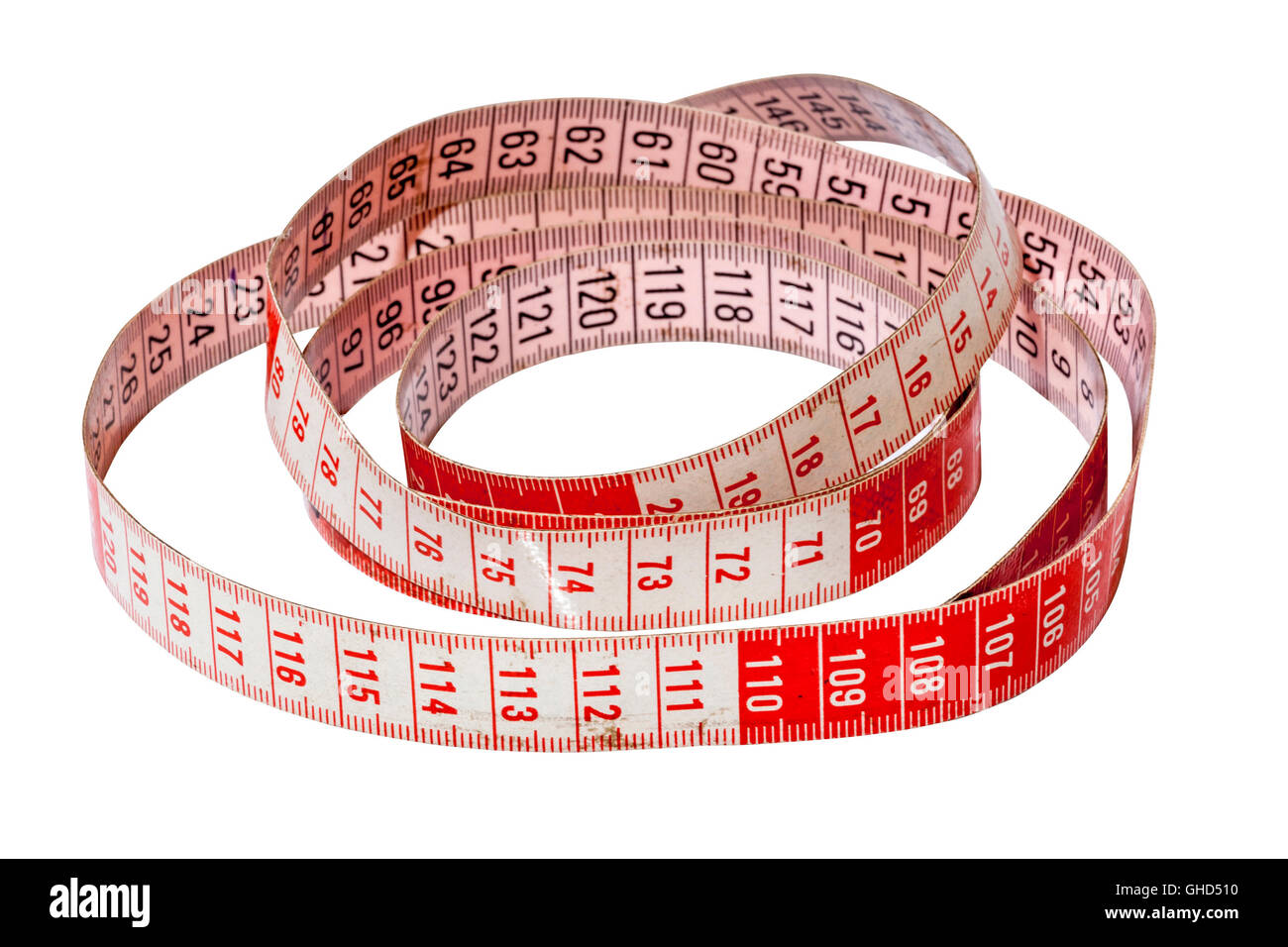 Studio shot isolated coiled red and white dressmaking tape measure marked in centimeters on white - Stock Image