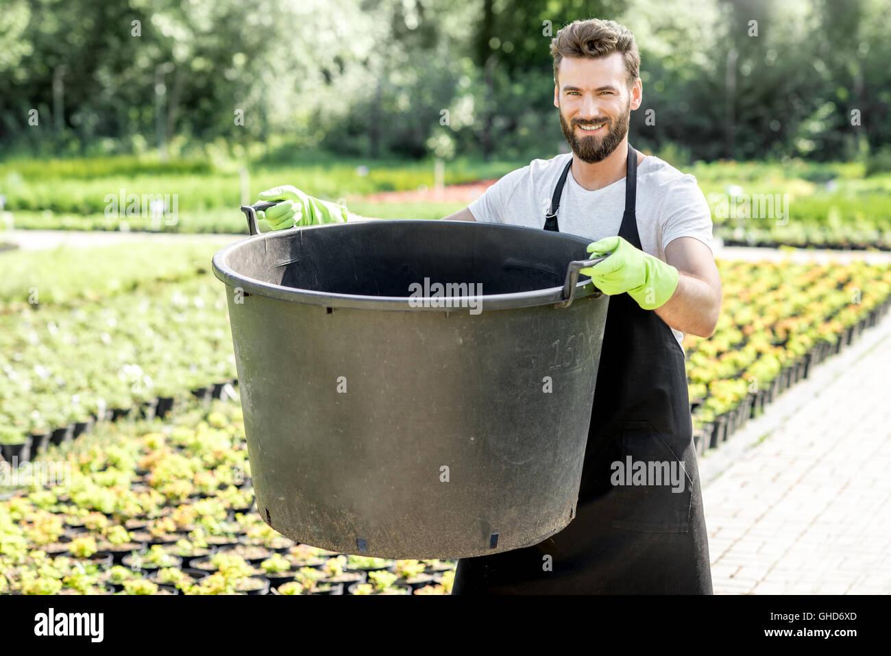 Handsome gardener with huge bucket - Stock Image