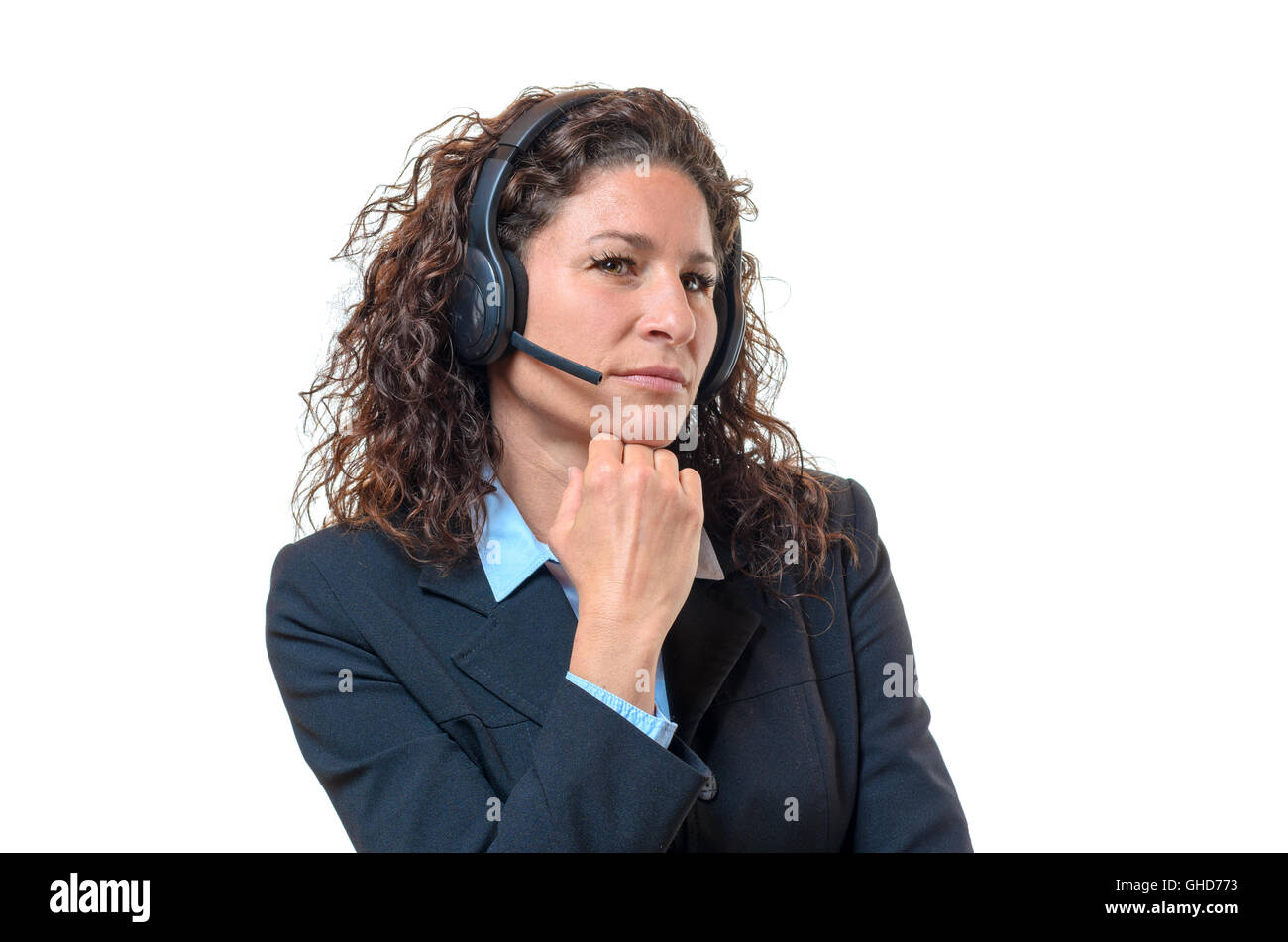 Speculative attractive young businesswoman wearing a headset looking sideways at the camera with a serious distrustful - Stock Image
