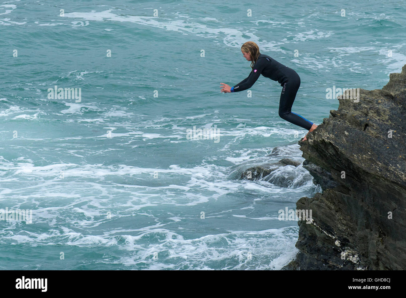 A teenager tombstoning off cliffs on Towan Headland in Newquay, Cornwall. - Stock Image
