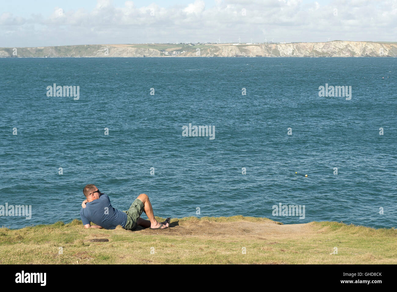 A holidaymaker relaxes on Towan Headland in Newquay, Cornwall. - Stock Image
