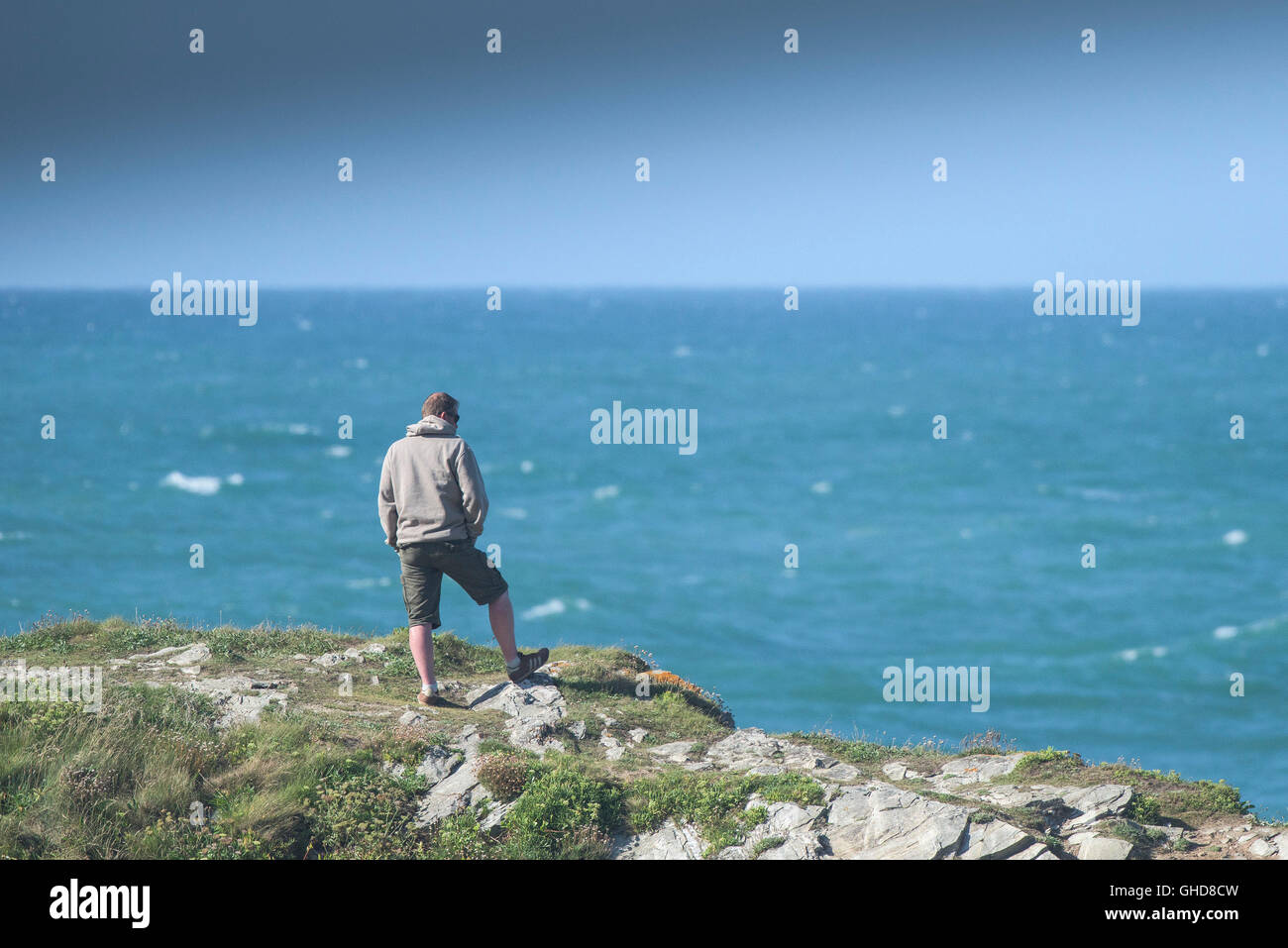 A holidaymaker enjoys the view as he stands on the rocks of Towan Headland in Newquay, Cornwall. - Stock Image