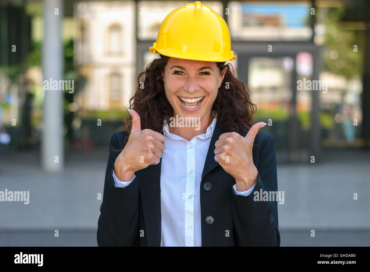 Motivated happy young female architect wearing a yellow hardhat giving a double thumbs up with a beaming smile to Stock Photo